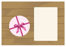 Gift Box with Pink Bow and  Sheet of paper  on Wooden Plank Background. Stock Photo