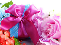 Gift box with pink ribbon bow and beautiful colorful flowers background Royalty Free Stock Photography