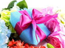 Gift box with pink ribbon bow and beautiful colorful flowers background Royalty Free Stock Photos