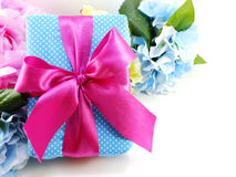Gift box with pink ribbon bow and beautiful colorful flowers background Stock Images