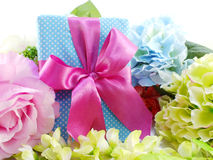 Gift box with pink ribbon bow and beautiful colorful flowers background Royalty Free Stock Image