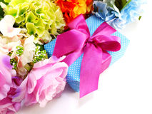 Gift box with pink ribbon bow and beautiful colorful flowers background Stock Photo