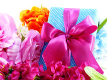 Gift box with pink ribbon bow and beautiful colorful flowers background Stock Photography