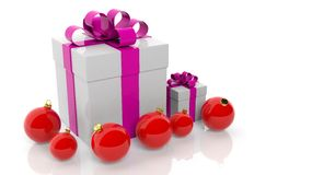 Gift box with pink ribbon and red Christmas balls. On white Royalty Free Stock Images