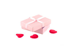 Gift box with a pink ribbon and red hearts. On a white background Stock Images