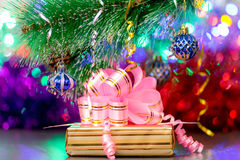 Gift box with pink ribbon under branch of christmas tree with decoration Royalty Free Stock Photos