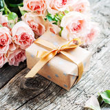 Gift Box and Pink Roses on Wooden Table Royalty Free Stock Images