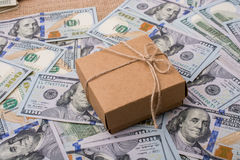 Gift box placed on spread US dollar banknotes. Gift box placed  is placed on spread US dollar banknotes Royalty Free Stock Images