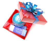 Gift box with planet earth inside and airplane tickets Stock Image