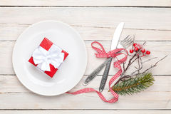 Gift box on plate, silverware and christmas decor Royalty Free Stock Photography