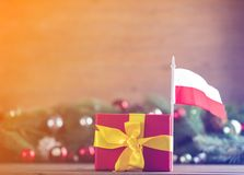 Gift box with Poland flag and pine cones. And branches on background. Image with Christmas holiday theme Royalty Free Stock Photography