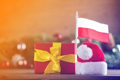 Gift box with Poland flag and Santa Claus hat. With pine cones and branches on background. Image with Christmas holiday theme Stock Photo