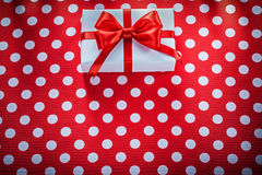 Gift box on polka-dot red fabric celebrations concept Stock Photos