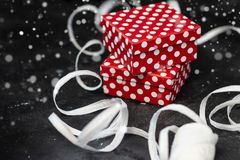 Gift box with polka dots and white ribbon on black surface. royalty free stock image