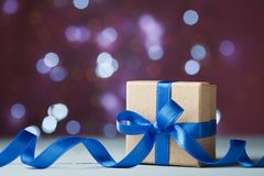 Gift box or present against festive bokeh background. Holiday greeting card for Christmas, New Year or birthday. Stock Photo