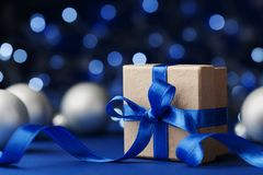 Gift box or present and christmas balls against blue bokeh background. Magic holiday greeting card. Royalty Free Stock Image