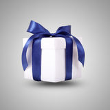 Gift box, present over grey background. White gift box with blue ribbon bow, isolated Stock Image