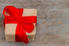 Gift box present with red bow ribbon and brown krafts wrapping p Royalty Free Stock Photography