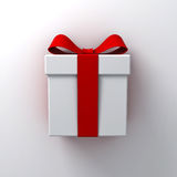 Gift box present with red ribbon bow on white wall background Stock Images