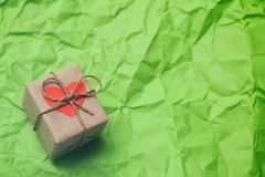 Gift box. Present wrapped in craft paper and tie hemp cord. Heart carton card. Green crumpled paper background.