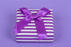 Gift box on purple Stock Images