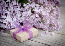 Gift box with purple bow and lilac on wood Royalty Free Stock Images