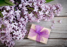 Gift box with purple bow and lilac on wood Stock Image