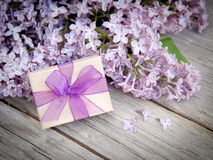 Gift box with purple bow and lilac on wood Stock Images