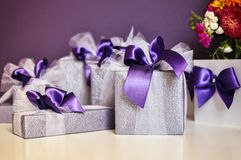 Gift box with purple bows on white table Royalty Free Stock Images
