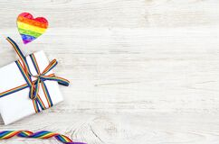 Gift box with rainbow LGBT ribbon on a light wooden background