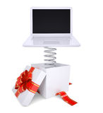 Gift box with red band and laptop Stock Photos