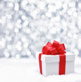 Gift box with red bow. Decorative white gift box with a large red bow standing in fresh snow against a background bokeh of twinkling party lights Royalty Free Stock Photo