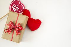 Gift box with red bow, red fluffy hearts and heart shaped lollipop. Gift box with red bow, red fluffy hearts and lollipop with i love you inscription. Present Stock Image