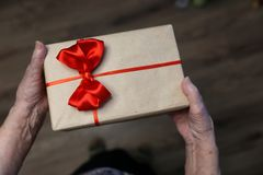 Gift box with red bow in grandmother hands. A color background concept for different holidays stock image