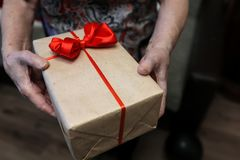 Gift box with red bow in grandmother hands. Macro royalty free stock photos