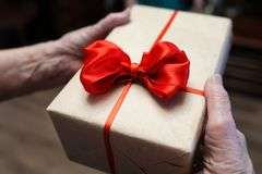 Gift box with red bow in grandmother hands. Macro stock images