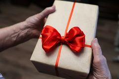 Gift box with red bow in grandmother hands. Macro royalty free stock photo