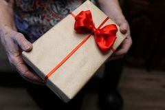 Gift box with red bow in grandmother hands. Macro royalty free stock images