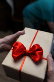 Gift box with red bow in grandmother hands. Macro royalty free stock photography