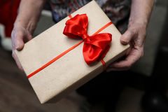 Gift box with red bow in grandmother hands. Macro stock image
