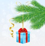 Gift box with a red bow hangs on the branch of christmas tree Royalty Free Stock Photography