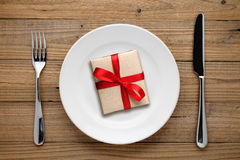 Gift box with red bow on plate Royalty Free Stock Photos