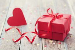Gift box with red bow ribbon and paper heart on table for Valentines day Stock Photos