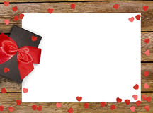 Gift box with red bow ribbon and paper heart on wooden background for Valentines day Royalty Free Stock Photos