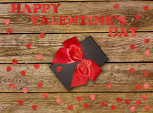Gift box with red bow ribbon and paper heart on wooden table for Valentines day Stock Photos
