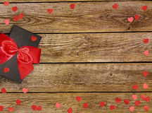 Gift box with red bow ribbon and paper heart on wooden table for Valentines day Stock Photography