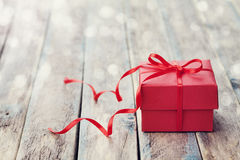 Gift box with red bow ribbon on wooden table for Valentines day Stock Photography