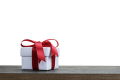 Gift box with red bow on rustic table for border Royalty Free Stock Image