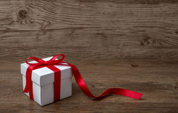 Gift box with red bow on rustic table, christmas or another celebration.  Stock Photo