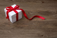 Gift box with red bow on rustic table, christmas or another celebration.  Royalty Free Stock Photos